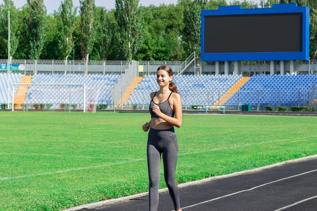 Jovem mulher que corre no estádio da pista de corridas. Foto Premium