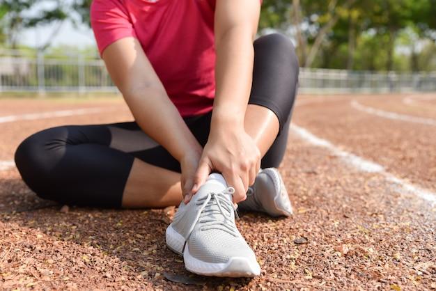 Jovem mulher que guarda o tornozelo na dor na trilha do estádio. ferimento running articulado torcido quebrado do esporte. Foto Premium