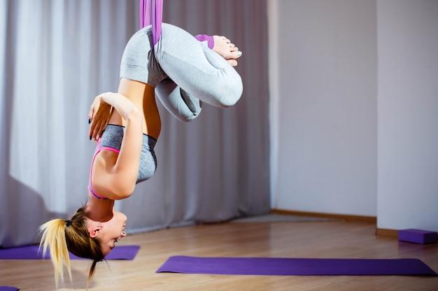 Jovem mulher que levanta fazendo o exercício aéreo da ioga com rede de cabeça para baixo. Foto Premium