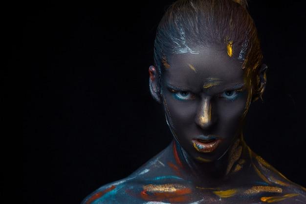 Jovem mulher que posa coberta com tinta preta Foto gratuita