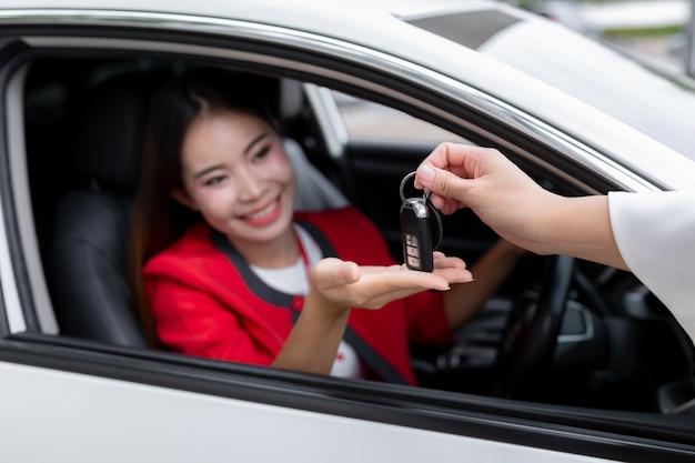 Jovem mulher que recebe as chaves de seu carro novo, Foto Premium
