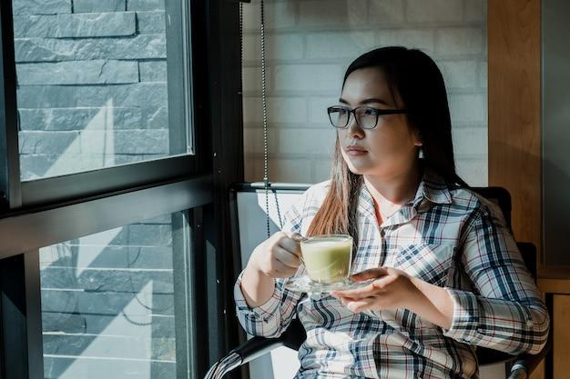 Jovem mulher que senta-se na cafetaria e no café bebendo. Foto Premium