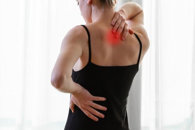 Jovem mulher que sofre de dor no pescoço e dor nas costas, esticando os músculos em casa. dor nas costas e pescoço mulher Foto Premium