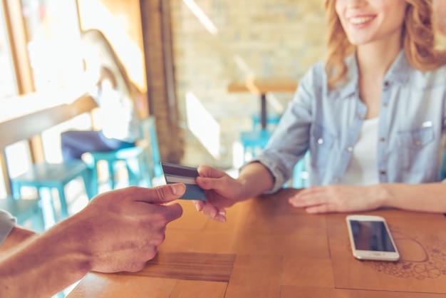 Jovem mulher que sorri ao dar um cartão de crédito Foto Premium