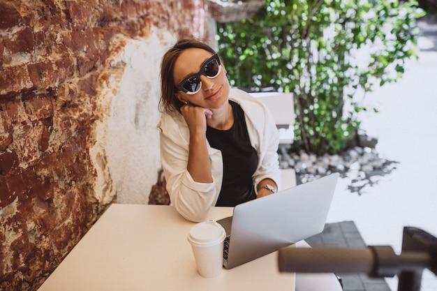 Jovem mulher que trabalha no laptop em um café Foto gratuita