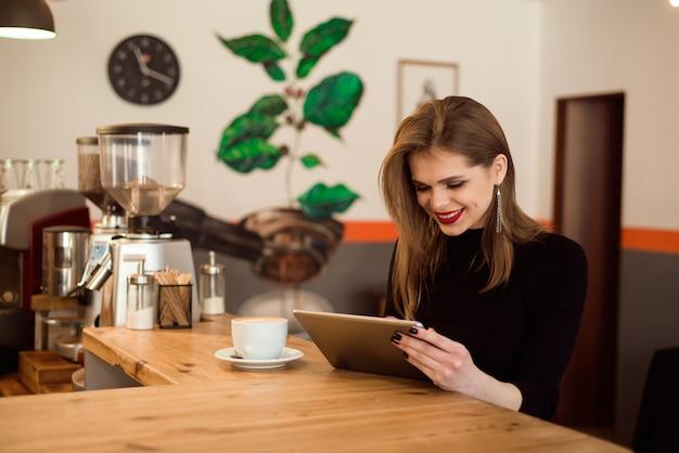 Jovem mulher que usa o tablet pc em um café. Foto Premium