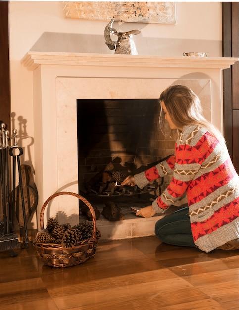 Jovem mulher queimando lareira com palito de fósforo em casa Foto gratuita