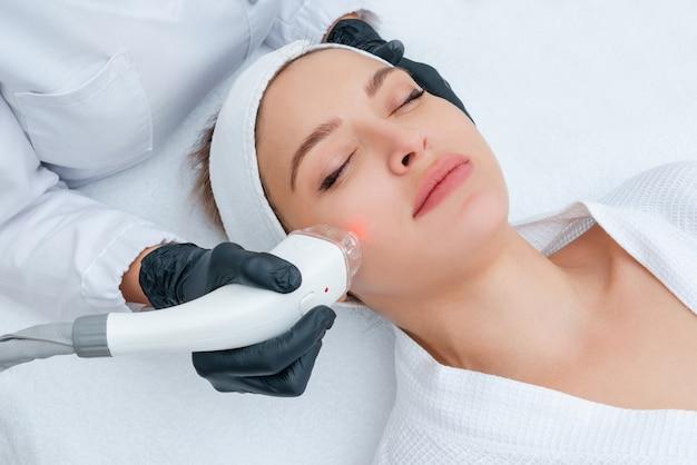 Jovem mulher recebendo tratamento a laser na clínica de cosmetologia Foto Premium
