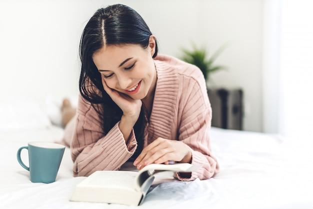 Jovem mulher relaxando e lendo o livro na cama em casa Foto Premium