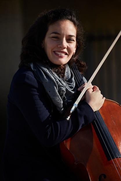 Jovem mulher rindo feliz com seu instrumento Foto gratuita