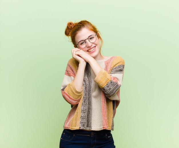 Jovem mulher ruiva bonita se sentindo apaixonado e bonito, adorável e feliz, sorrindo romanticamente com as mãos ao lado do rosto contra a parede verde Foto Premium