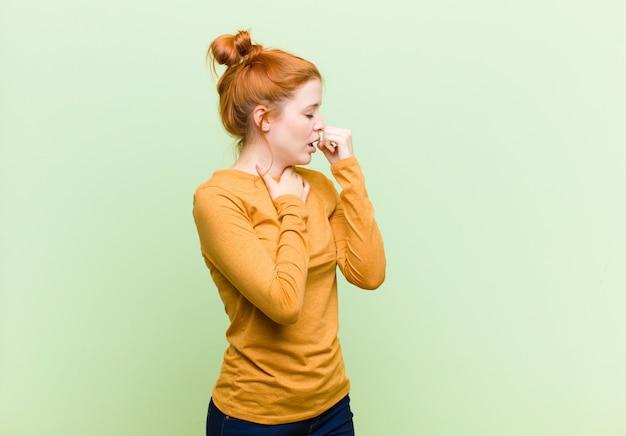 Jovem mulher ruiva bonita sentindo-se mal com sintomas de dor de garganta e gripe, tossindo com a boca coberta contra a parede verde Foto Premium