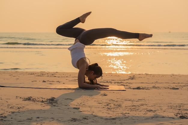 Jovem mulher saudável yoga praticando yoga pose na praia ...