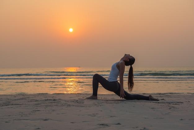 Jovem mulher saudável yoga praticando yoga pose na praia ao nascer do sol Foto Premium