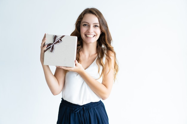 Jovem mulher segurando a caixa de presente com fita a sorrir Foto gratuita