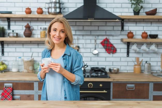 Jovem, mulher, segurando a caneca de café na mão de pé na cozinha Foto gratuita
