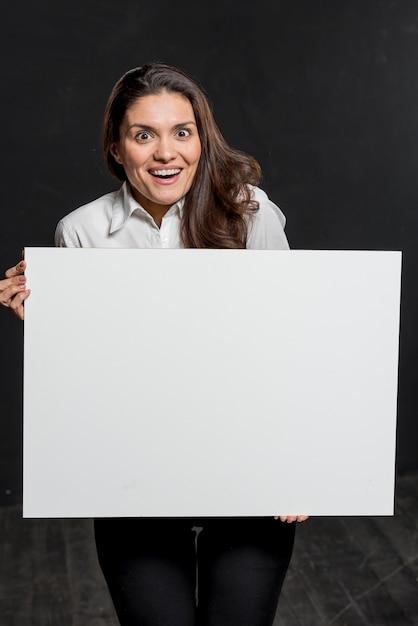 Jovem mulher segurando a folha de papel em branco Foto gratuita