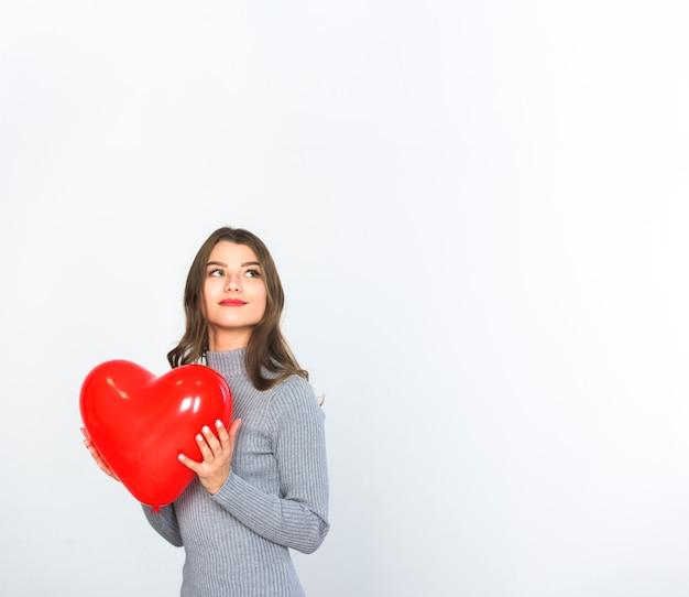 Jovem mulher segurando balão de coração vermelho nas mãos Foto gratuita