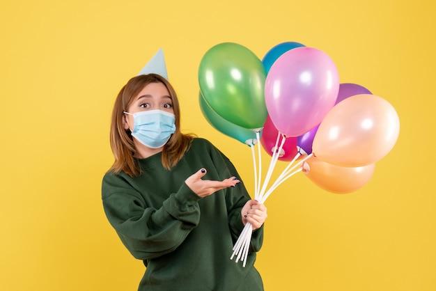 Jovem mulher segurando balões coloridos Foto gratuita