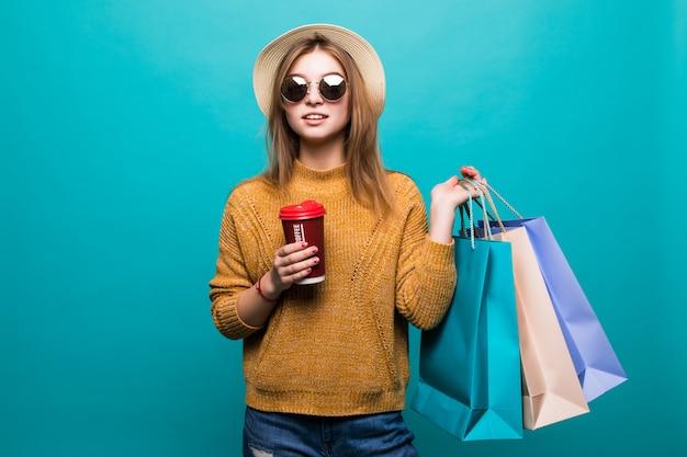 Jovem mulher segurando café para ir e sacolas de compras enquanto sorrindo na parede azul Foto gratuita
