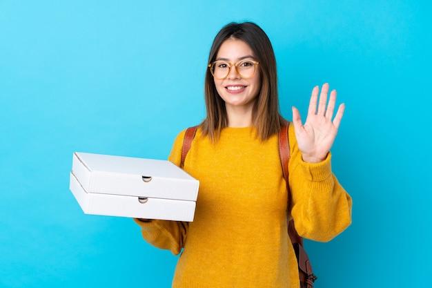 Jovem mulher segurando caixas de pizza sobre parede azul isolada Foto Premium