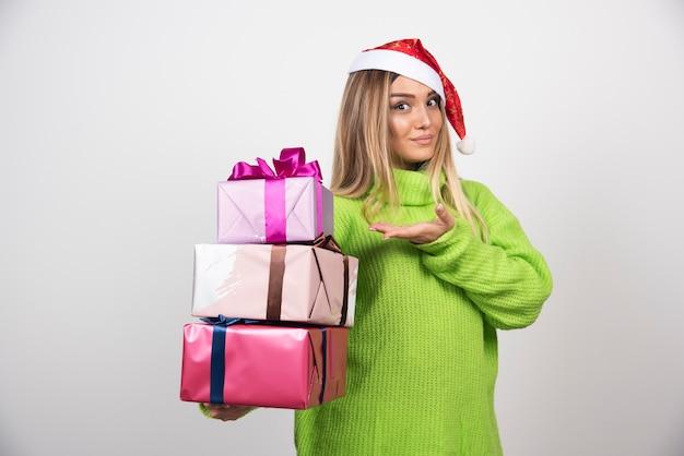 Jovem mulher segurando nas mãos presentes de natal festivos. Foto gratuita