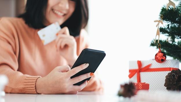 Jovem mulher segurando o cartão de crédito e fazendo compras on-line. Foto Premium