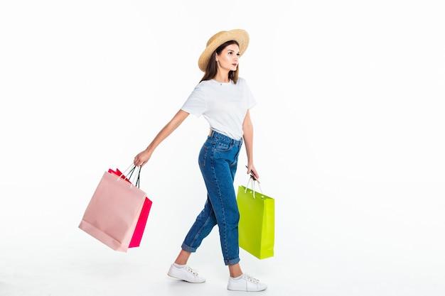 Jovem mulher segurando sacos coloridos isolados na parede branca Foto gratuita