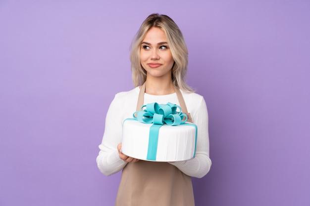 Jovem mulher segurando um bolo Foto Premium
