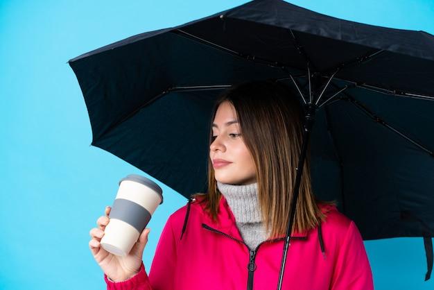 Jovem mulher segurando um guarda-chuva e café para tirar sobre parede azul isolada Foto Premium