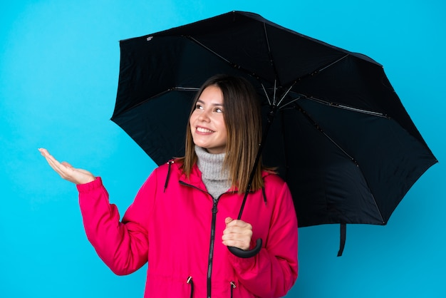 Jovem mulher segurando um guarda-chuva sobre parede azul isolada Foto Premium