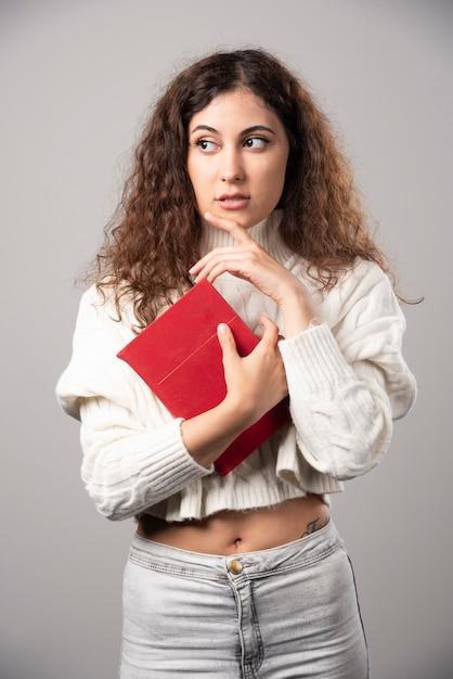 Jovem mulher segurando um livro vermelho em uma parede cinza. foto de alta qualidade Foto gratuita