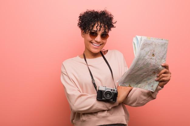 Jovem mulher segurando um mapa sorrindo confiante com braços cruzados Foto Premium