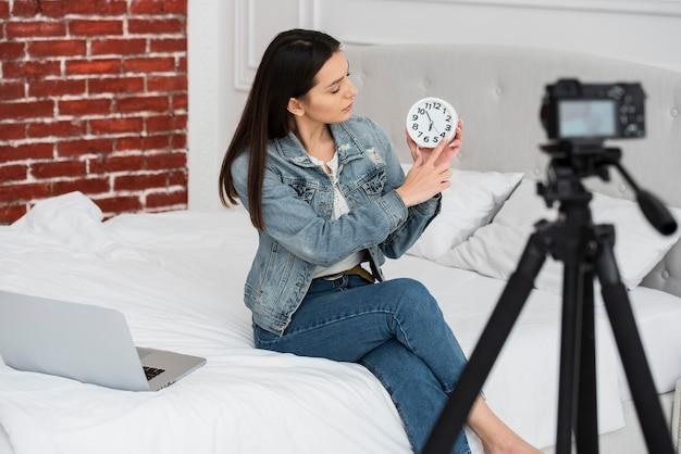 Jovem mulher segurando um relógio Foto gratuita