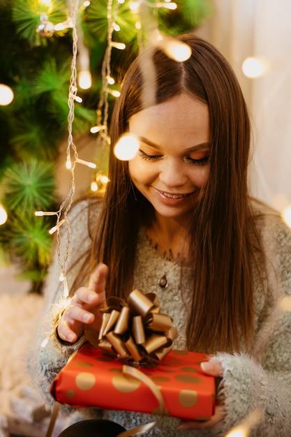 Jovem mulher segurando uma árvore de natal Foto gratuita