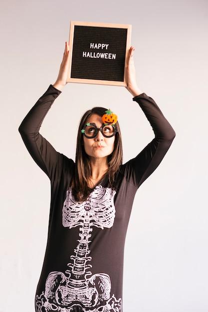 Jovem mulher segurando uma placa de carta vintage preto com sinal de feliz dia das bruxas. estilo de vida dentro de casa. traje esqueleto Foto Premium