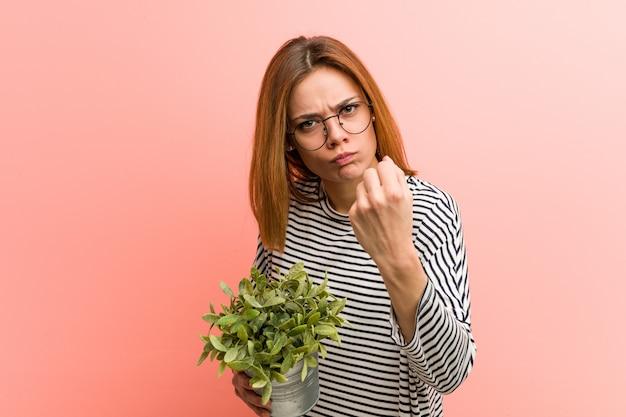 Jovem mulher segurando uma planta mostrando o punho para a câmera, expressão facial agressiva Foto Premium