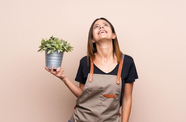 Jovem mulher segurando uma planta olhando para cima enquanto sorrindo Foto Premium