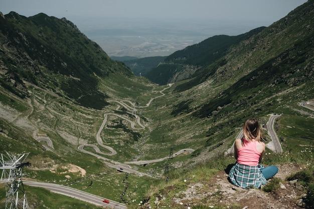 Jovem mulher sentada à beira do penhasco, olhando de cima na estrada da montanha transfegerasan. Foto gratuita