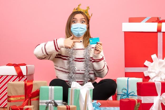 Jovem mulher sentada de frente para o natal apresenta com cartão do banco Foto gratuita