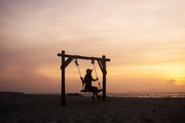 jovem-mulher-sentada-em-um-balanco-na-praia-com-o-ceu-do-sol_42299-190.jpg