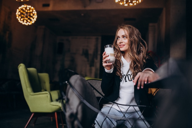 Jovem mulher sentada em uma cadeira dentro de um café Foto gratuita