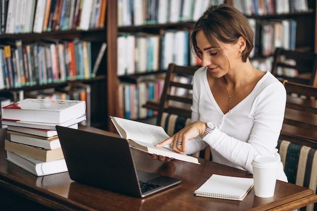 Jovem mulher sentada na biblioteca usando livros e computador Foto gratuita