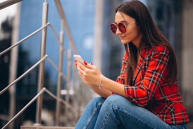 Jovem mulher sentada na escada e falando ao telefone Foto gratuita