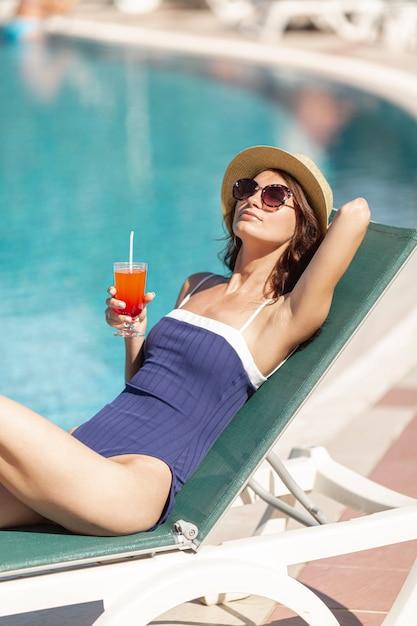 Jovem mulher sentada na espreguiçadeira um cocktail na margem da piscina Foto gratuita