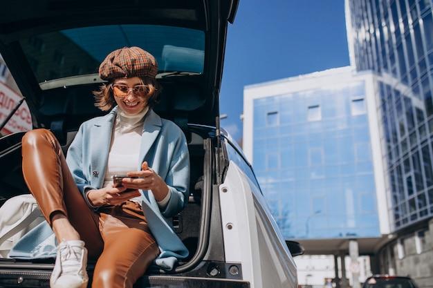 Jovem mulher sentada na parte de trás do carro falando ao telefone Foto gratuita