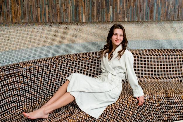 Jovem mulher sentada na sauna e sorrindo Foto Premium