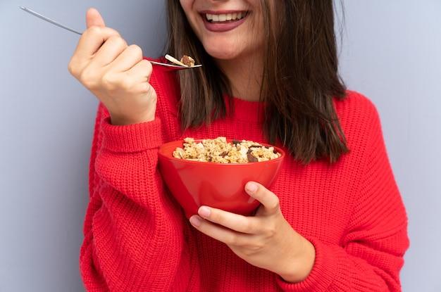 Jovem mulher sentada no chão e segurando uma tigela de cereais Foto Premium