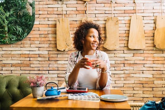 Jovem mulher sentada no restaurante segurando copo de suco Foto gratuita