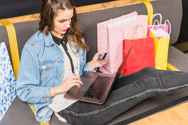 Jovem mulher sentada no sofá de compras on-line com cartão de débito Foto gratuita